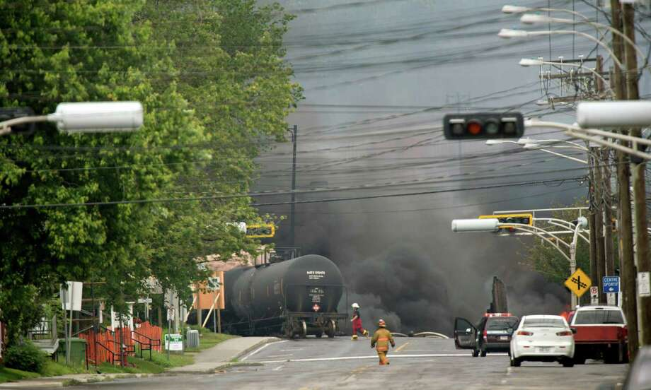 Smoke rises from railway cars that were carrying crude oil after derailing in downtown Lac Megantic, Quebec, Canada, Saturday, July 6, 2013. The derailment sparked several explosions and forced the evacuation of up to 1,000 people. Photo: AP