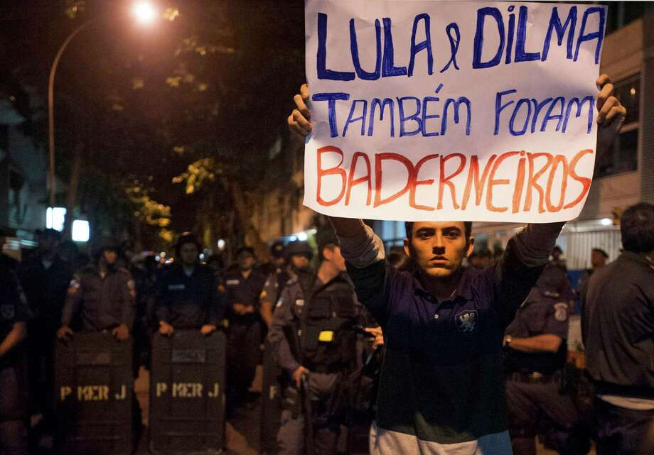 """A protestor holds a sign that reads """"Lula and Dilma were also rioters"""" while police officers stand guard in front of Rio de Janeiro's Governor Sergio Cabral's house in Rio de Janeiro, Brazil, July 4, 2013. The wave of protests that hit Brazil on June 17 began as opposition to transportation fare hikes, then expanded to include anger at high taxes, poor services, and high spending for the World Cup. Demonstrations eventually coalesced around the issue of rampant government corruption. Photo: AP"""