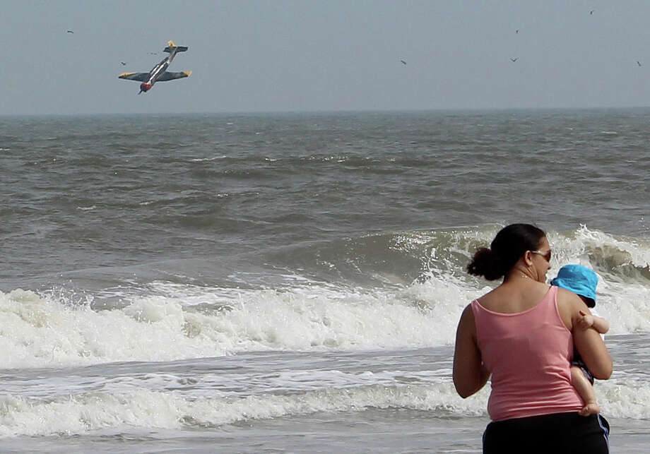 In this Sunday, June 30, 2013 photo released by  Lisa Rufo, a woman holds her child as a plane crashes into the Atlantic Ocean with two off-duty police officers off the beach from Ocean City Md. Troopers say the plane took off from the Ocean City Municipal Airport between 3:30 p.m. and 3:45 p.m. Sunday. The destination is not known. Investigators believe Thomas J. Geoghegan Jr., who owned the single-engine Nanchang CJ-6A, was piloting it and 27-year-old Joshua D. Adickes, the lone passenger, was seated behind him. Photo: AP