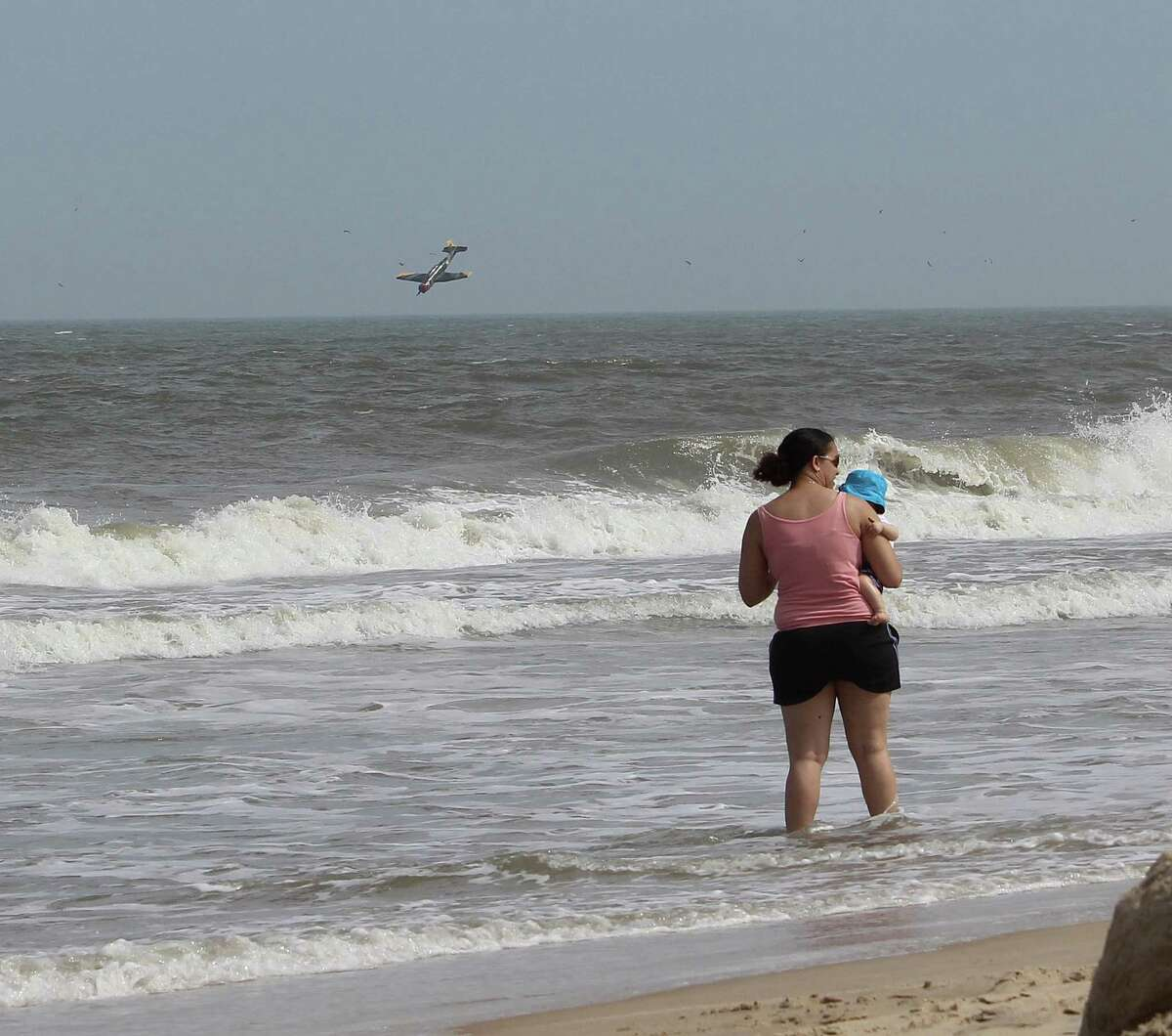 In this Sunday, June 30, 2013 photo released by Lisa Rufo, a woman holds her child as a plane crashes into the Atlantic Ocean with two off-duty police officers off the beach from Ocean City Md. Troopers say the plane took off from the Ocean City Municipal Airport between 3:30 p.m. and 3:45 p.m. Sunday. The destination is not known. Investigators believe Thomas J. Geoghegan Jr., who owned the single-engine Nanchang CJ-6A, was piloting it and 27-year-old Joshua D. Adickes, the lone passenger, was seated behind him.