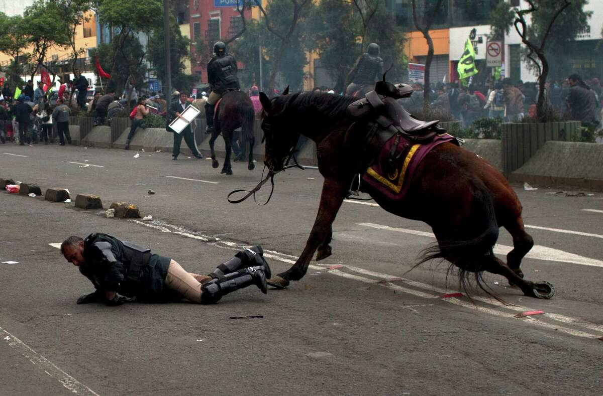 A policeman tries to recover after falling from his horse during a protest against the new civil service law that will require government employees to undergo work evaluations, in Lima, Peru, Thursday, July 4, 2013. After a total of 20 hours of debates and months of modifications, Peru's Congress approved the new civil service law with 59 votes in favor, 45 against and 3 abstentions.