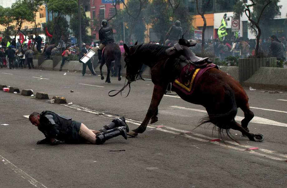 A policeman tries to recover after falling from his horse during a protest against the new civil service law that will require government employees to undergo work evaluations, in Lima, Peru, Thursday, July 4,  2013. After a total of 20 hours of debates and months of modifications, Peru's Congress approved the new civil service law with 59 votes in favor, 45 against and 3 abstentions. Photo: AP