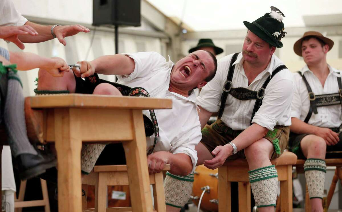 A man dressed in traditional clothes tries to pull his opponent over the table during the Alps Finger Wrestling championships in Mittenwald, southern Germany, Sunday, July 7, 2013. Competitors battled for the title in this traditional rural sport where the winner has to pull his opponent over a marked line on the table.
