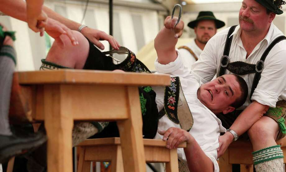A man dressed in traditional clothes tries to pull his opponent over the table during the Alps Finger Wrestling championships in Mittenwald, southern Germany, Sunday, July 7, 2013. Competitors battled for the title in this traditional rural sport where the winner has to pull his opponent over a marked line on the table. Photo: AP