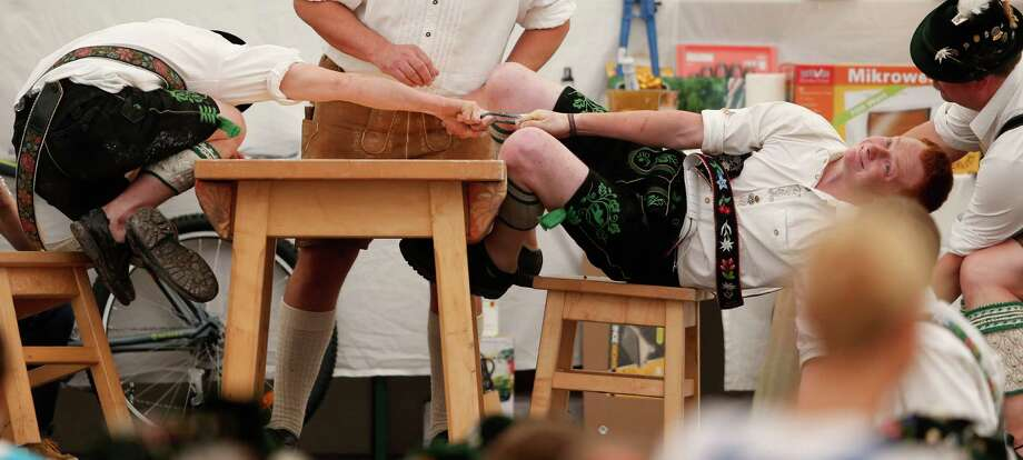 Men dressed in traditional clothes try to pull their opponents over the table during the Alps Finger Wrestling championships in Mittenwald, southern Germany, Sunday, July 7, 2013. Competitors battled for the title in this traditional rural sport where the winner has to pull his opponent over a marked line on the table. Photo: AP
