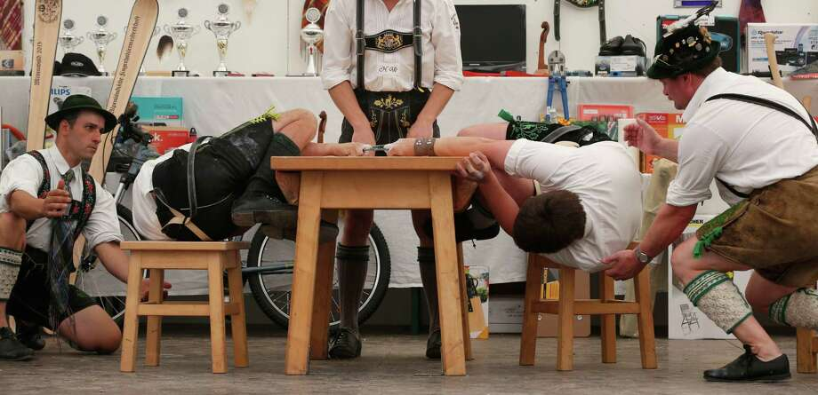 Men dressed in traditional clothes try to pull their opponent over the table during the Alps Finger Wrestling championships in Mittenwald, southern Germany, Sunday, July 7, 2013. Competitors battled for the title in this traditional rural sport where the winner has to pull his opponent over a marked line on the table. Photo: AP