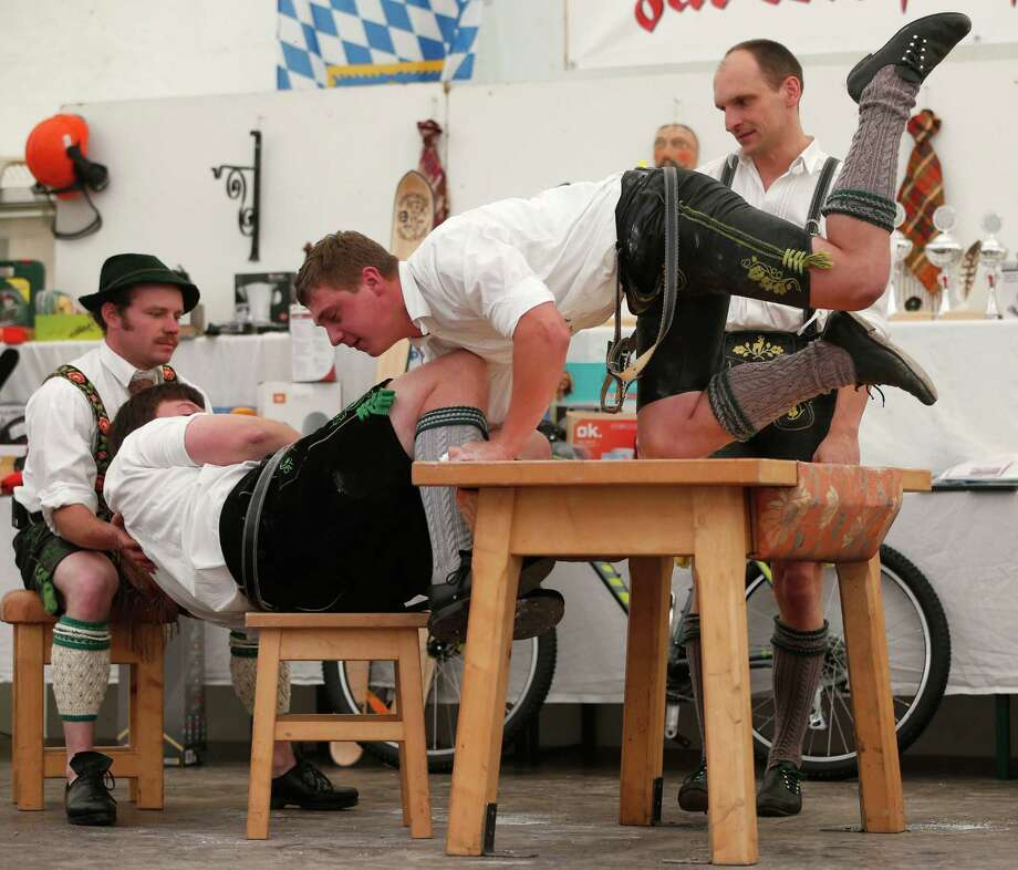 A man dressed in traditional clothes pulls his opponent over the table during the Alps Finger Wrestling championships in Mittenwald, southern Germany, Sunday, July 7, 2013. Competitors battled for the title in this traditional rural sport where the winner has to pull his opponent over a marked line on the table. Photo: AP