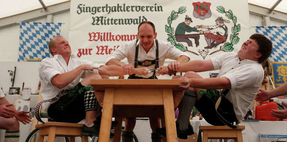 A judge watches the leather ring held by two competitors with their middle fingers at the Alps Finger Wrestling championships in Mittenwald, southern Germany, Sunday, July 7, 2013. Competitors battled for the title in this traditional rural sport where the winner has to pull his opponent over a marked line on the table. Photo: AP