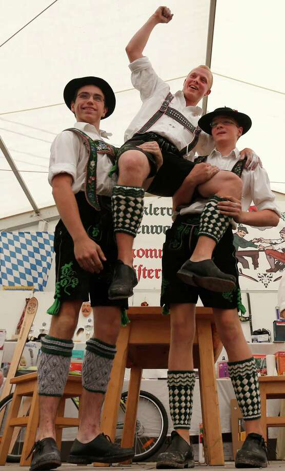 A young man dressed in traditional clothes celebrates with others after winning his fight at the Alps Finger Wrestling championships in Mittenwald, southern Germany, Sunday, July 7, 2013. Competitors battled for the title in this traditional rural sport where the winner has to pull his opponent over a marked line on the table. Photo: AP