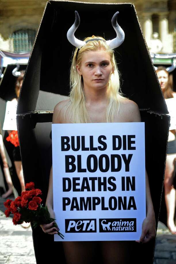 Activists of the pro-animal groups People for the Ethical Treatment of Animals (PETA) and Anima Naturalis stand in coffins that represent the 48 bulls that will be killed during the San Fermin festivities in the Northern Spanish city of Pamplona on July 5, 2013 during an anti-bullfighting protest.  The San Fermin festival is a symbol of Spanish culture that attracts thousands of tourists to watch the bull runs despite heavy condemnation from animal rights groups.  Photo: RAFA RIVAS, Getty Images / 2013 AFP