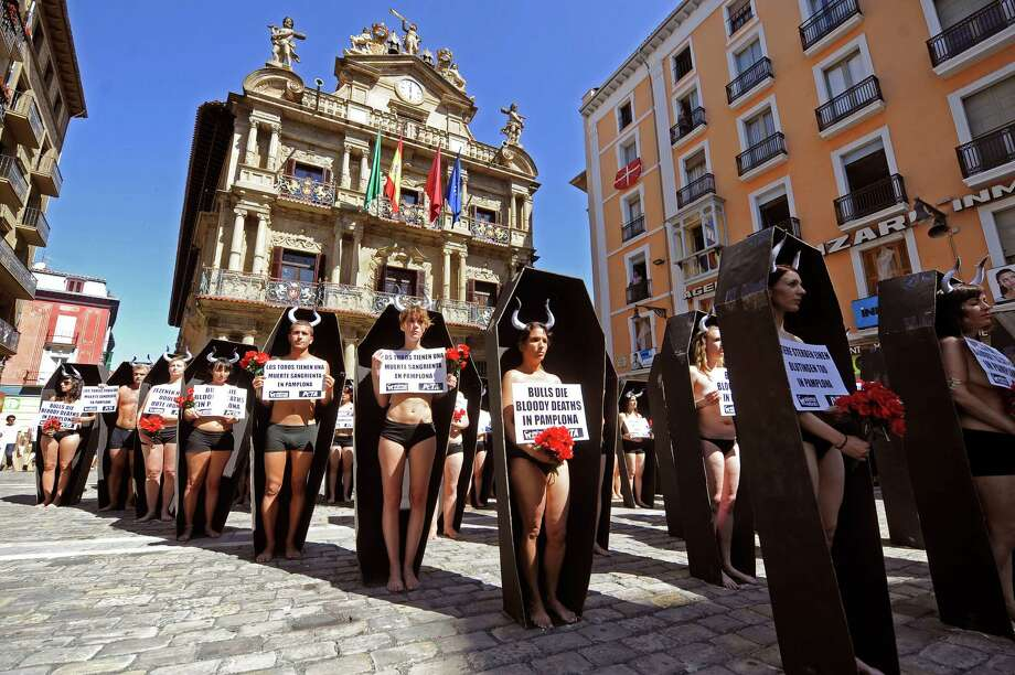 Activists of the People for the Ethical Treatment of Animals (PETA) and Anima Naturalis pro-animal groups stand in coffins that represent the 48 bulls that will be killed during the San Fermin festivities in the Northern Spanish city of Pamplona on July 5, 2013 during an anti-bullfighting protest.  The San Fermin festival is a symbol of Spanish culture that attracts thousands of tourists to watch the bull runs despite heavy condemnation from animal rights groups. Photo: RAFA RIVAS, Getty Images / 2013 AFP