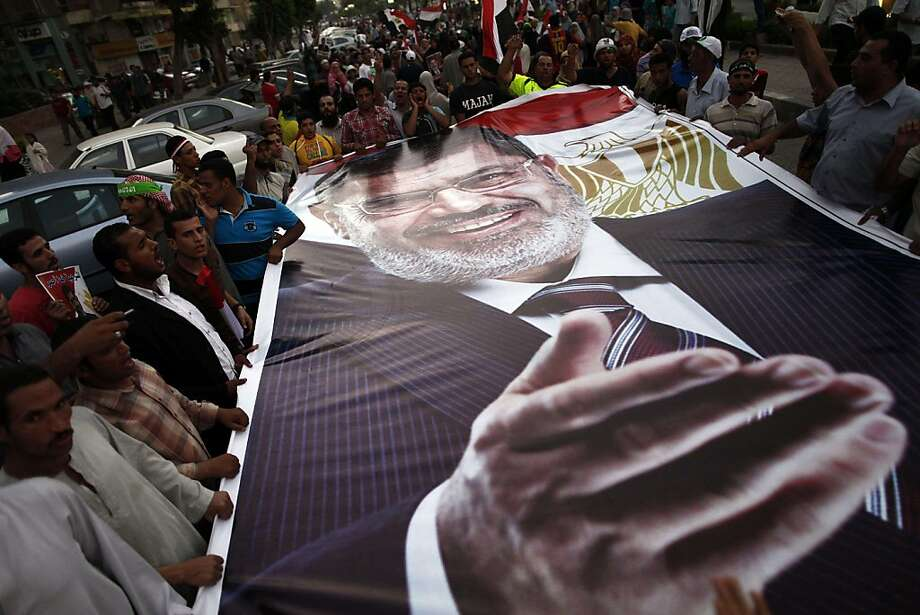 Ousted President Mohammed Morsi supporters and Muslim Brotherhood members hold a giant portrait of him as they demonstrate against his toppling. Photo: Mahmoud Khaled, AFP/Getty Images