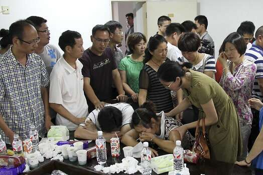 Parents of Wang Linjia, center, are comforted by parents of some other students who were on the Asiana Airlines Flight 214 that crashed at San Francisco International Airport, at Jiangshan Middle School in Jiangshan city, in eastern China's Zhejiang province, Sunday July 7, 2013. Chinese state media have identified the two people who died in the plane crash at San Francisco International Airport on Saturday as Ye Mengyuan and Wang Linjia, students at Jiangshan Middle School in China's eastern Zhejiang province. (AP Photo)  CHINA OUT Photo: Uncredited, Associated Press