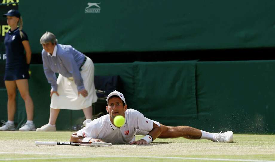 Novak Djokovic of Serbia looks at the ball after slipping as he plays Andy Murray of Britain during the Men's singles final match at the All England Lawn Tennis Championships in Wimbledon, London, Sunday, July 7, 2013. Photo: AP