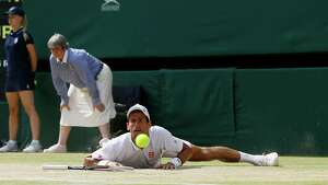 Novak Djokovic of Serbia looks at the ball after slipping as he plays Andy Murray of Britain during the Men's singles final match at the All England Lawn Tennis Championships in Wimbledon, London, Sunday, July 7, 2013.