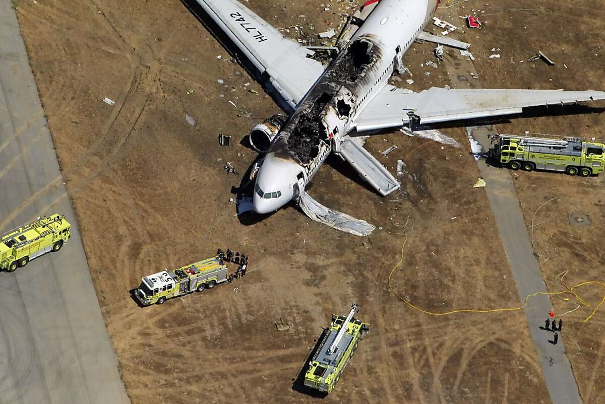 Fire trucks surround the destroyed fuselage of Asiana Airlines Flight 214 as it sits on the runway at San Francisco International Airport after it crashed on landing and burned on Saturday, July 6, 2013.