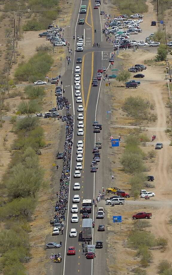 Thousands turn out to mourn as a somber procession of 19 hearses bearing the 19 firefighters passes through the desert. Photo: Mark J. Terrill, Associated Press