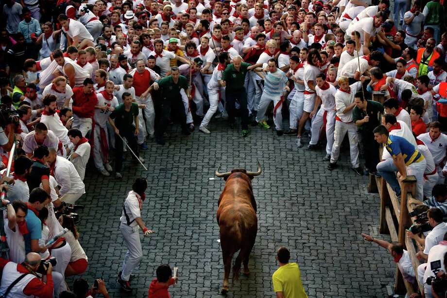 An Alcurrucen's ranch fighting bull runs towards revelers during the running of the bulls of the San Fermin festival, on Sunday, in Pamplona, Spain. Revelers from around the world arrive to Pamplona every year to take part on some of the eight days of the running of the bulls. Photo: Daniel Ochoa De Olza, STF / AP