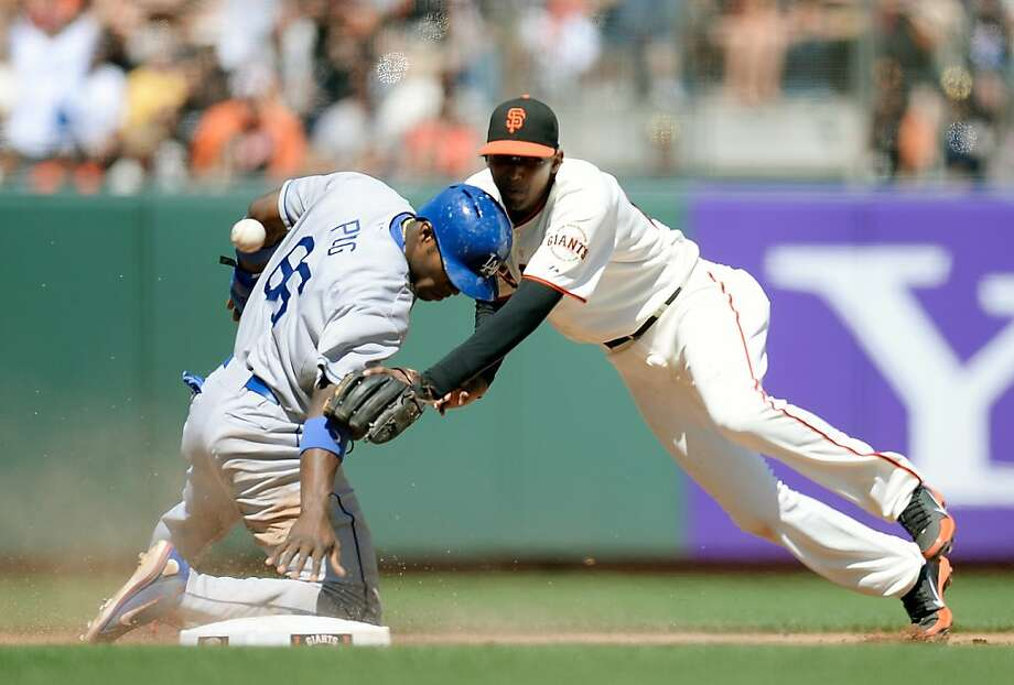 Joaquin Arias (right) dives as Buster Posey's throw sails past Yasiel Puig, who got up and went to third. Photo: Thearon W. Henderson, Getty Images