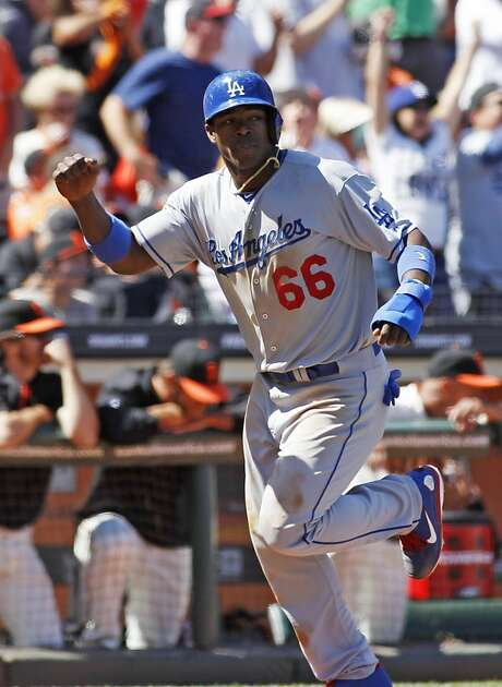 Yasiel Puig scores the Dodgers' go-ahead run in the ninth inning after leading off against Sergio Romo with a single. Photo: George Nikitin, Associated Press