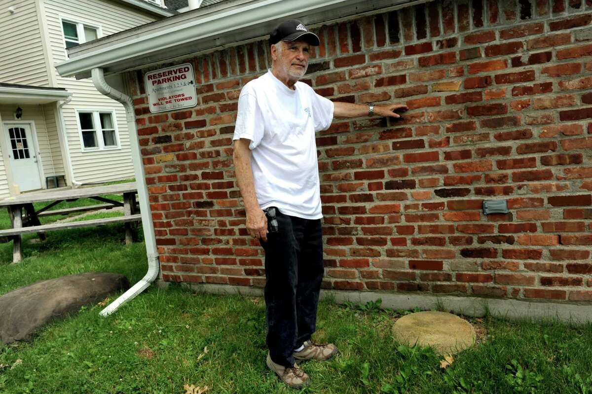 Property owner Joe Seger indicates the height of his stolen anchor, which weighs as much as 500 pounds, on Tuesday, June 25, 2013, at Reges Apartments in Albany, N.Y. Seger is seeking help in finding the stolen ship's anchor that has sentimental value to him. (Cindy Schultz / Times Union)