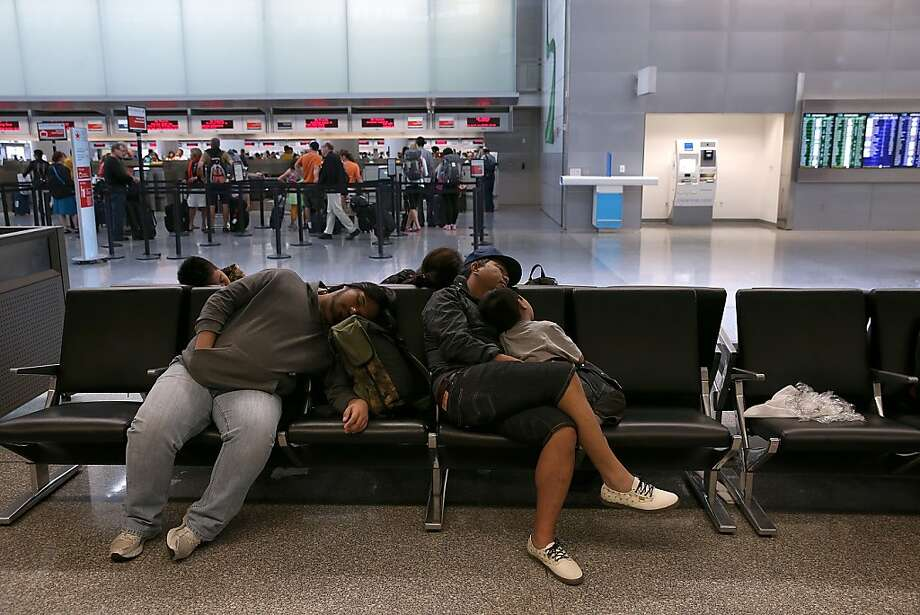 Stranded passengers sleep on benches at San Francisco International Airport, where flight delays and cancellations continue. Photo: Justin Sullivan, Getty Images