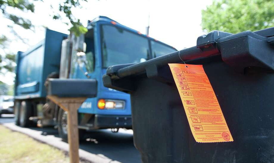 A ticket on the can lets residents know their trash is in violation. Cans need to be a minimum distance from each other and obstacles so the electric arm can grab the can. Photo: Nick De La Torre, Staff / © 2013  Houston Chronicle