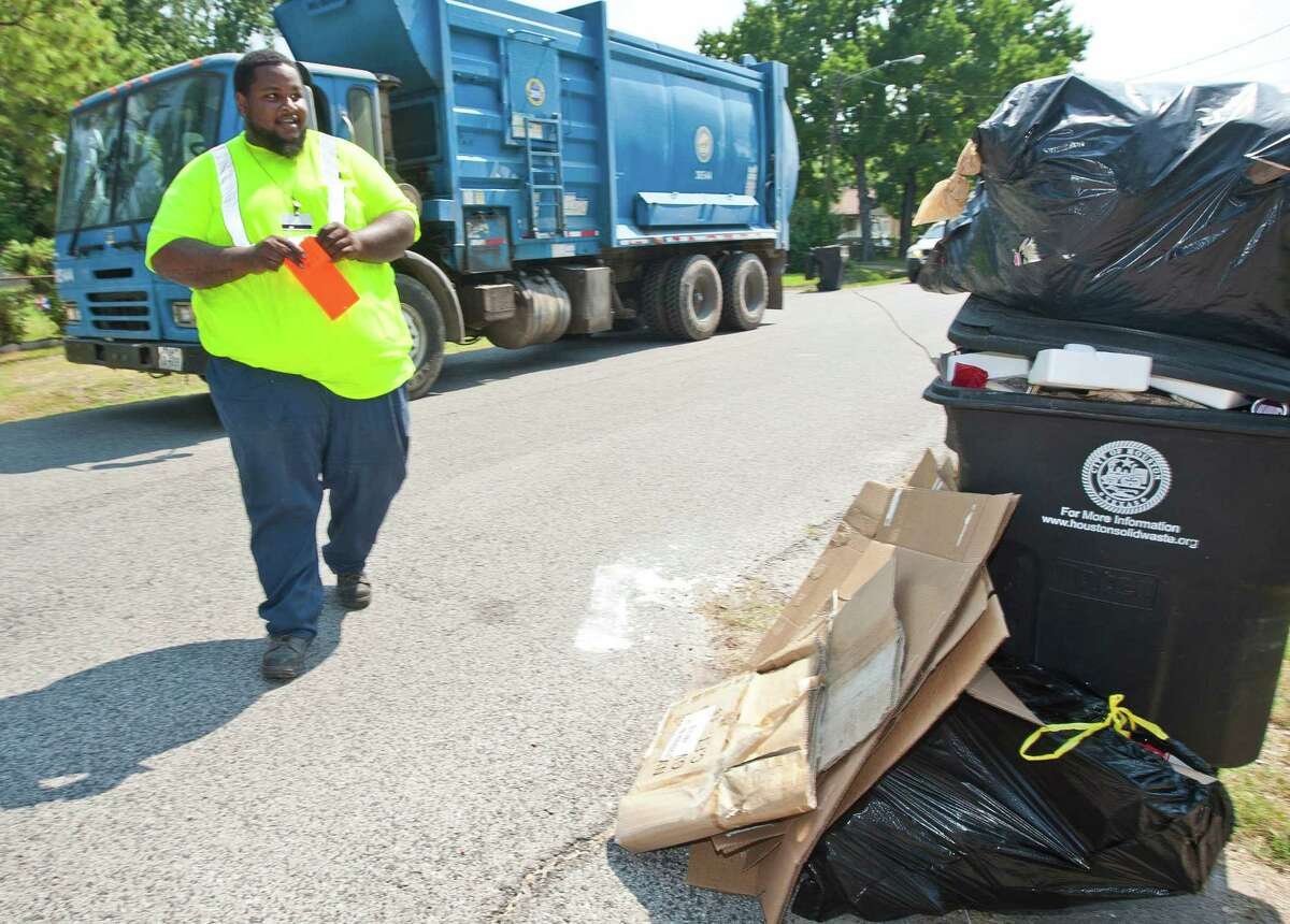 Derrick Colomb, with the city's solid waste department, writes a ticket because customers have trash outside of the can.