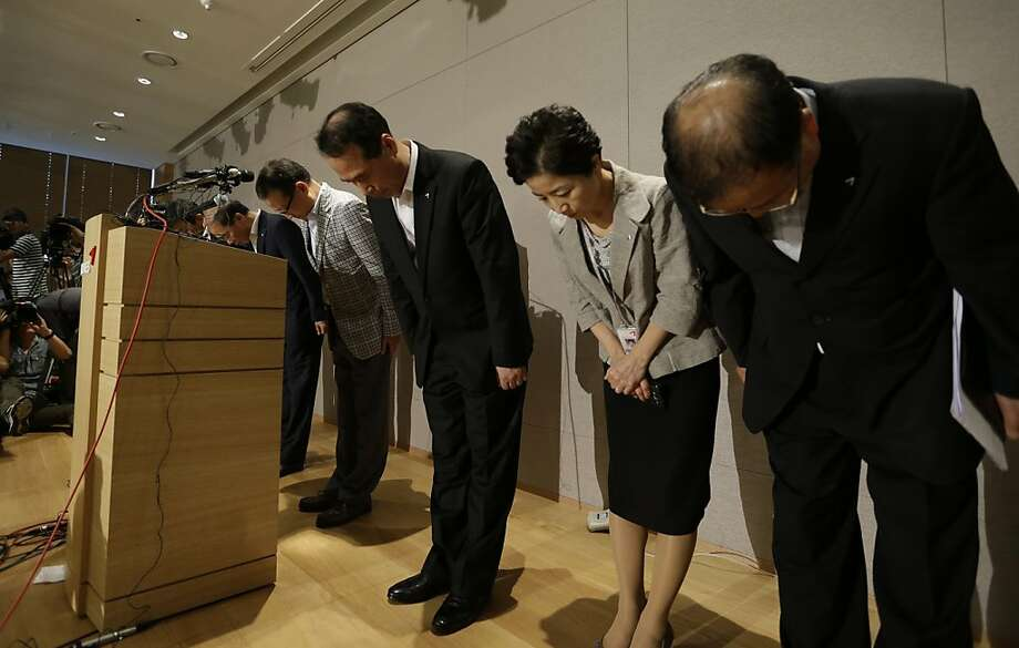 Asiana Airlines executives bow during a press conference after  the Asiana Airlines flight crash at SFO on July 7, 2013. The airlines was fined $500,000 today for failing to help family members of passengers who were on the plane that crashed. Photo: Lee Jin-man, Associated Press