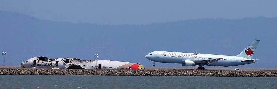 An Air Canada jet passes the wreckage of Asiana Airlines Flight 214 as it lands Sunday at San Francisco International Airport. The Asiana jet came close to stalling as it approached the runway, and the pilot tried to abort the landing, investigators said. Two people died. Photo: Aric Crabb, MBR / Oakland Tribune