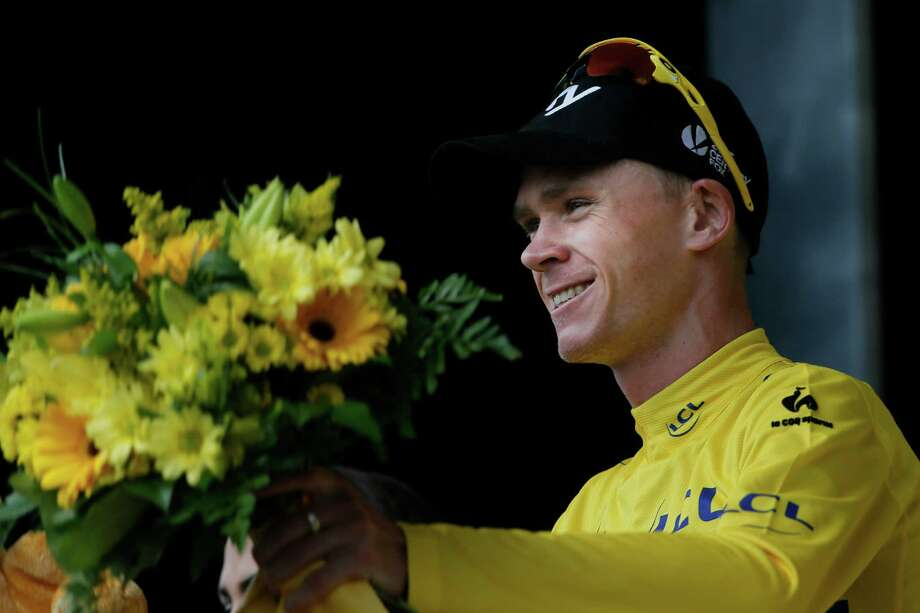 Christopher Froome of Britain, wearing the overall leader's yellow jersey, celebrates on the podium of the ninth stage of the Tour de France cycling race over 168.5 kilometers (105.3 miles) with start in Saint-Girons and finish in Bagneres-de-Bigorre, Pyrenees region, France, Sunday July 7 2013. (AP Photo/Laurent Rebours) ORG XMIT: PDJ155 Photo: Laurent Rebours / AP