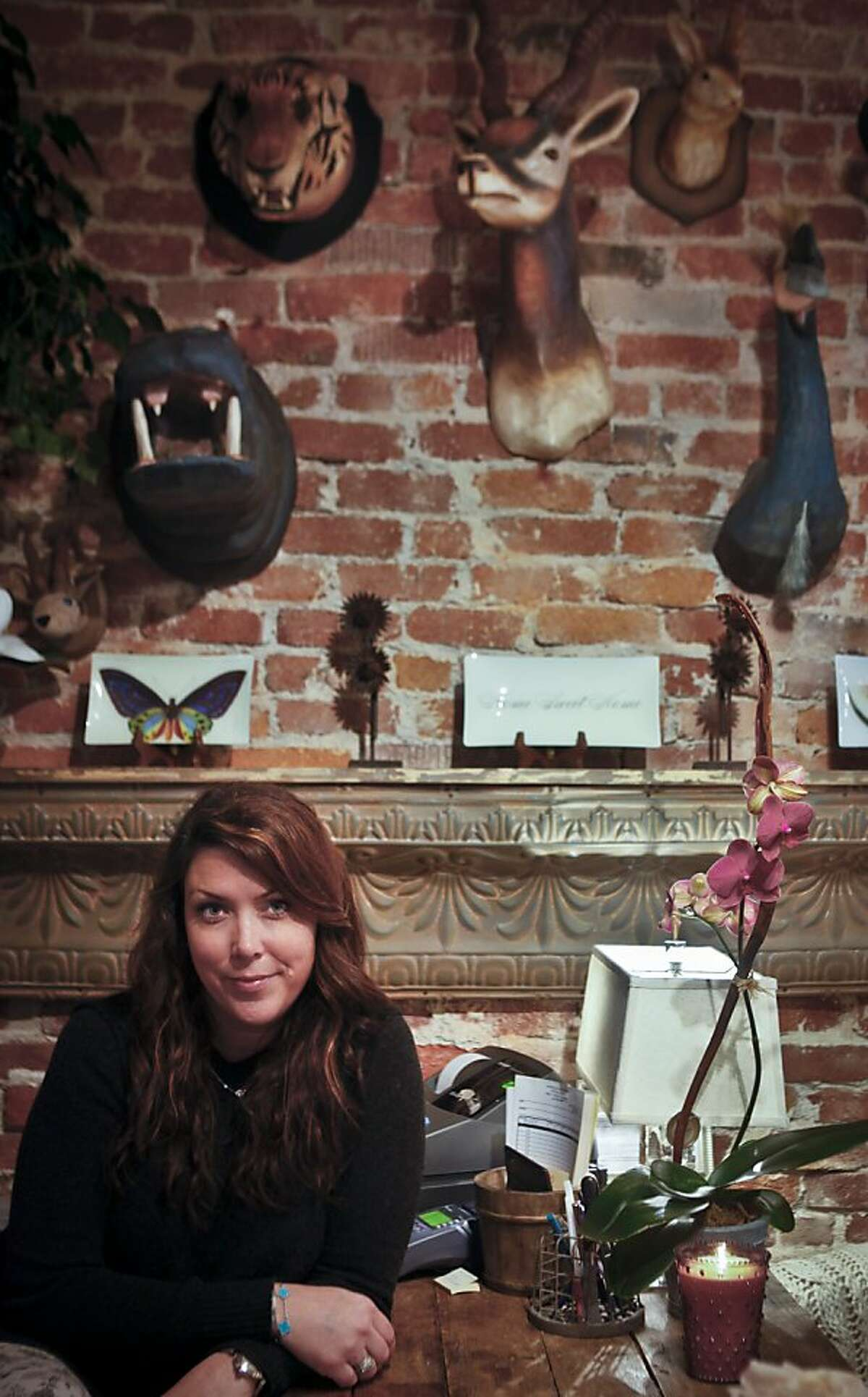 Tolan Florence, owner of Moss and Daughters, is seen in front of a wall of paper mache taxidermy in her Mill Valley, Calif., shop on Tuesday, March 13, 2012.