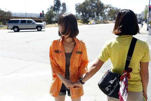 Hee Young, a survivor of the Asiana Boeing 777 crash landing, holds a friends hand after talking with the media outside of the Crowne Plaza hotel Burlingame, Calif. on July 7, 2013. Photo: Ian C. Bates, The Chronicle