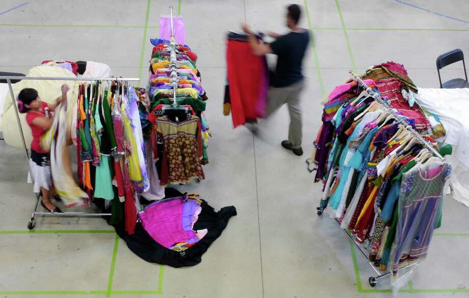 Aaminah Afzal, left, 9, helps her father, Aaquila Afzal, right, hang up clothing from Aaquila's store, Albany Fashions, at the Islamic Center of Capital District Eid Bazaar on Sunday, July 7, 2013 in Schenectady, NY.  The bazaar features vendors that have items for use in Ramadan and also for Eid festival which follows Ramadan.   (Paul Buckowski / Times Union) Photo: Paul Buckowski / 00023057A