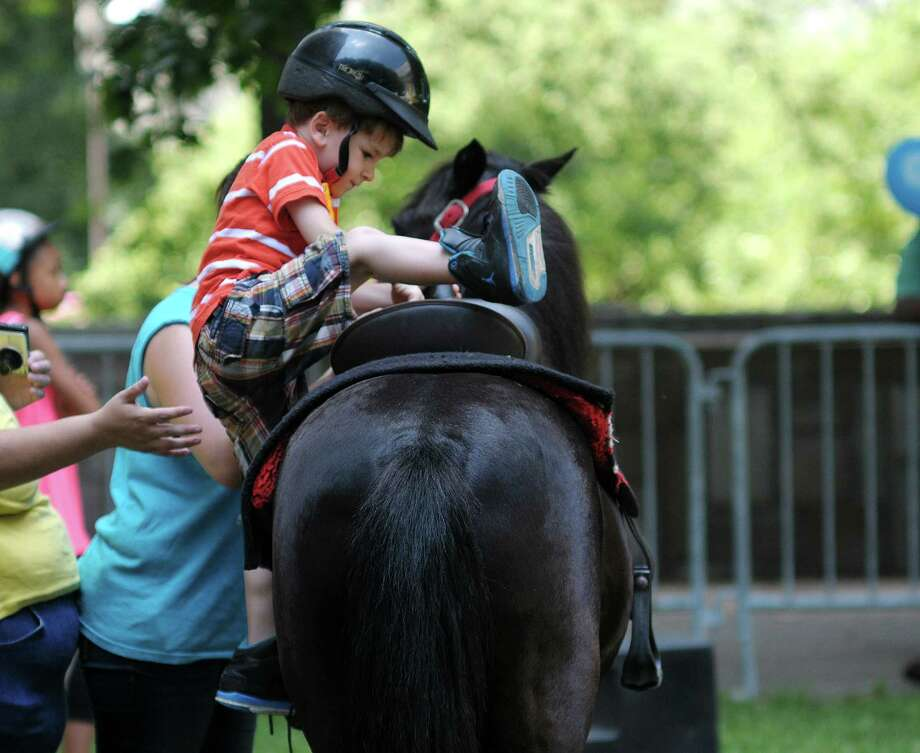 Aiden Woods, 5, of Rensselaer climbs aboard a pony for a ride at the  Empire State Plaza during GE's Kids Day on Sunday, July 7, 2013 in Albany, NY.  The yearly event is put on by GE and New York State Office of General Services.  (Paul Buckowski / Times Union) Photo: Paul Buckowski / 00023015A