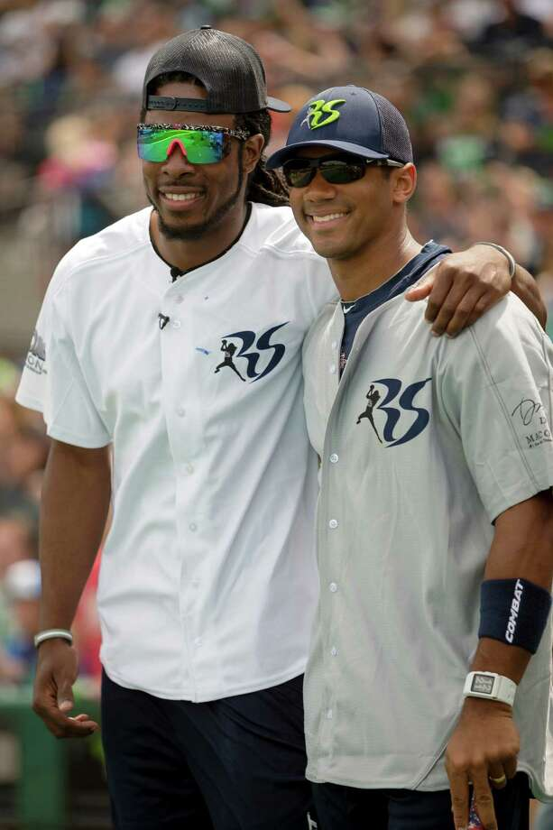 Seahawks cornerback Richard Sherman, left, and quarterback Russell Wilson, right, pose for pictures before the Richard Sherman Celebrity Softball Game Sunday, July 7, 2013, at Cheney Stadium in Tacoma, Wash. The family-friendly event featured a home run derby with a portion of all proceeds going to Blanket Coverage, The Richard Sherman Family Foundation and Homes for Heroes. Photo: JORDAN STEAD, SEATTLEPI.COM / SEATTLEPI.COM