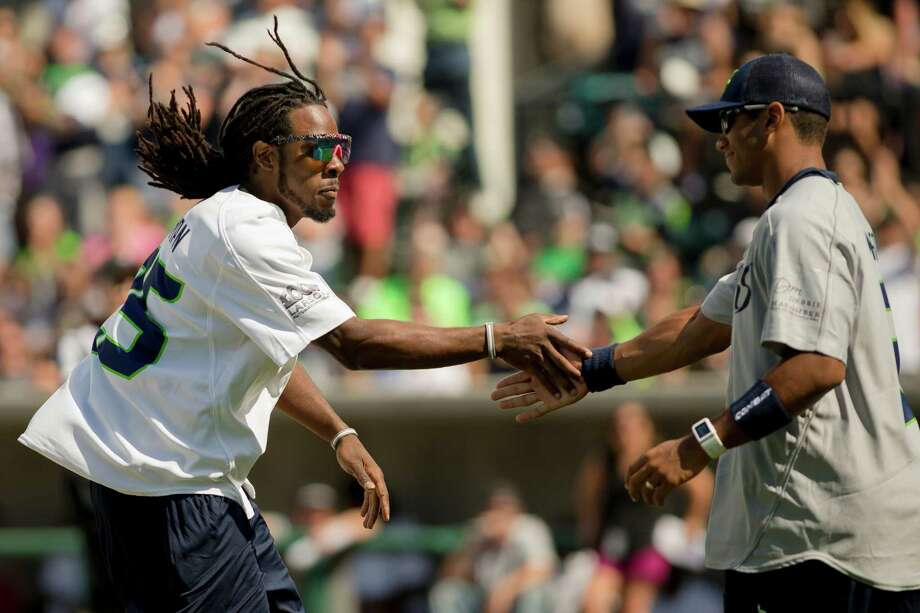 Seahawks cornerback Richard Sherman, left, gives quarterback Russell Wilson, right, a straight-faced handshake after hitting a home run during the Richard Sherman Celebrity Softball Game Sunday, July 7, 2013, at Cheney Stadium in Tacoma, Wash. The family-friendly event featured a home run derby with a portion of all proceeds going to Blanket Coverage, The Richard Sherman Family Foundation and Homes for Heroes. Photo: JORDAN STEAD, SEATTLEPI.COM / SEATTLEPI.COM