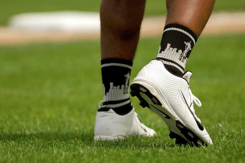 Russell Wilson shows his Seattle pride with some regionally-themed socks at the Richard Sherman Celebrity Softball Game Sunday, July 7, 2013, at Cheney Stadium in Tacoma, Wash. The family-friendly event featured a home run derby with a portion of all proceeds going to Blanket Coverage, The Richard Sherman Family Foundation and Homes for Heroes.