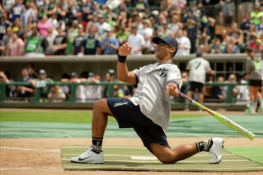 Seahawks quarterback Russell Wilson drops to a knee to watch his hit at the Richard Sherman Celebrity Softball Game Sunday, July 7, 2013, at Cheney Stadium in Tacoma, Wash. The family-friendly event featured a home run derby with a portion of all proceeds going to Blanket Coverage, The Richard Sherman Family Foundation and Homes for Heroes. Photo: JORDAN STEAD, SEATTLEPI.COM / SEATTLEPI.COM