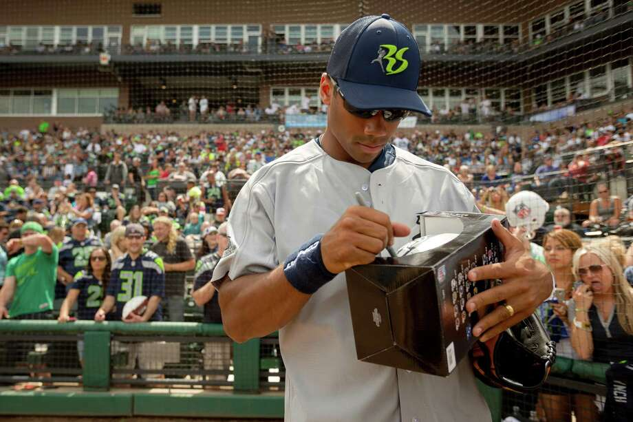 Russell Wilson autographs a football before the Richard Sherman Celebrity Softball Game Sunday, July 7, 2013, at Cheney Stadium in Tacoma, Wash. The family-friendly event featured a home run derby with a portion of all proceeds going to Blanket Coverage, The Richard Sherman Family Foundation and Homes for Heroes. Photo: JORDAN STEAD, SEATTLEPI.COM / SEATTLEPI.COM