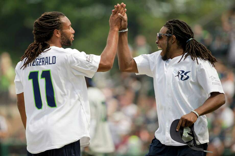 Seahawks cornerback Richard Sherman, right, reacts to a play by Larry Fitzgerald, left, during the Richard Sherman Celebrity Softball Game Sunday, July 7, 2013, at Cheney Stadium in Tacoma, Wash. The family-friendly event featured a home run derby with a portion of all proceeds going to Blanket Coverage, The Richard Sherman Family Foundation and Homes for Heroes. Photo: JORDAN STEAD, SEATTLEPI.COM / SEATTLEPI.COM
