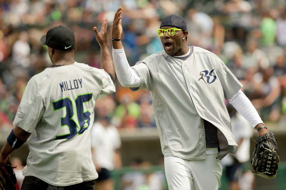 Terrell Owens, right, gives a backhanded high five to Lawyer Milloy, left, at the Richard Sherman Celebrity Softball Game Sunday, July 7, 2013, at Cheney Stadium in Tacoma, Wash. The family-friendly event featured a home run derby with a portion of all proceeds going to Blanket Coverage, The Richard Sherman Family Foundation and Homes for Heroes. Photo: JORDAN STEAD, SEATTLEPI.COM / SEATTLEPI.COM