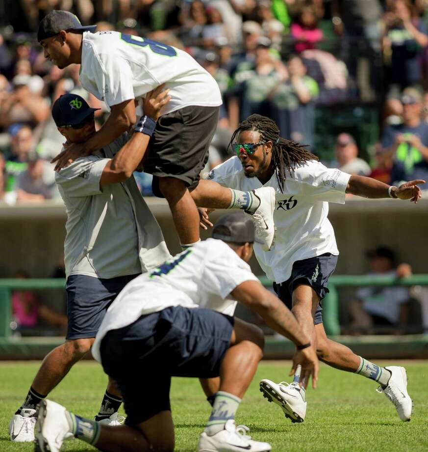 Seahawks cornerback Richard Sherman, right, attempts to sneak up on a faked pig pile and on-field confrontation regarding a botched play during the Richard Sherman Celebrity Softball Game Sunday, July 7, 2013, at Cheney Stadium in Tacoma, Wash. The family-friendly event featured a home run derby with a portion of all proceeds going to Blanket Coverage, The Richard Sherman Family Foundation and Homes for Heroes. Photo: JORDAN STEAD, SEATTLEPI.COM / SEATTLEPI.COM