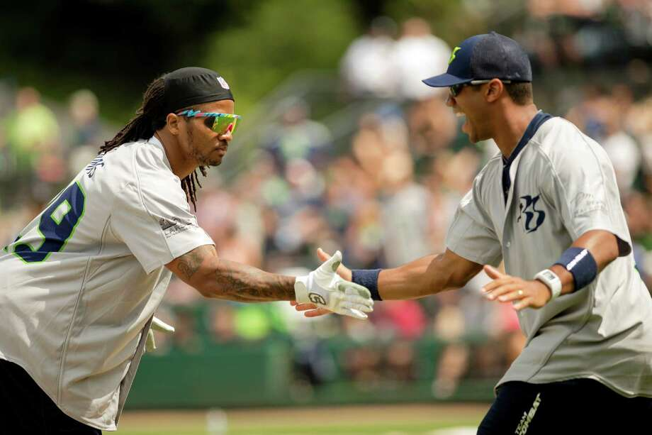 Seahawks players Earl Thomas, left, and Russell Wilson, right, share a handshake after a run for their team at the Richard Sherman Celebrity Softball Game Sunday, July 7, 2013, at Cheney Stadium in Tacoma, Wash. The family-friendly event featured a home run derby with a portion of all proceeds going to Blanket Coverage, The Richard Sherman Family Foundation and Homes for Heroes. Photo: JORDAN STEAD, SEATTLEPI.COM / SEATTLEPI.COM