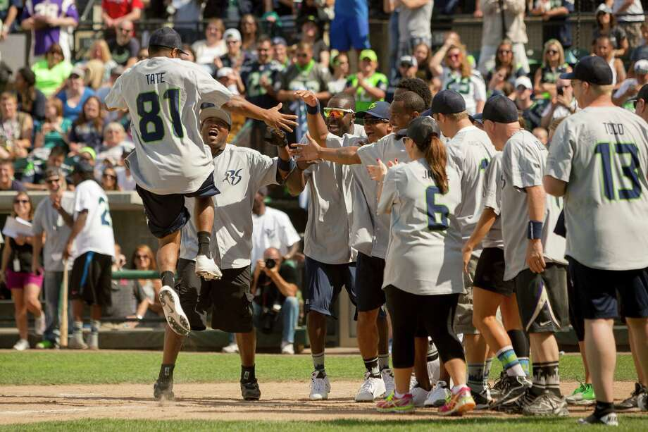 Golden Tate, left, leaps into the arms of his teammates after scoring a home run during the Richard Sherman Celebrity Softball Game Sunday, July 7, 2013, at Cheney Stadium in Tacoma, Wash. The family-friendly event featured a home run derby with a portion of all proceeds going to Blanket Coverage, The Richard Sherman Family Foundation and Homes for Heroes. Photo: JORDAN STEAD, SEATTLEPI.COM / SEATTLEPI.COM