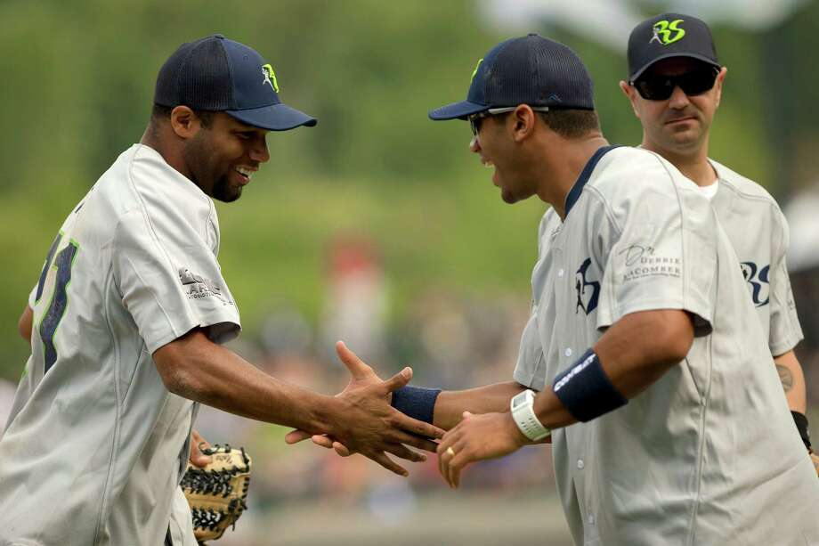 Golden Tate, left, and Russell Wilson, center right, share a handshake during the Richard Sherman Celebrity Softball Game Sunday, July 7, 2013, at Cheney Stadium in Tacoma, Wash. The family-friendly event featured a home run derby with a portion of all proceeds going to Blanket Coverage, The Richard Sherman Family Foundation and Homes for Heroes. Photo: JORDAN STEAD, SEATTLEPI.COM / SEATTLEPI.COM