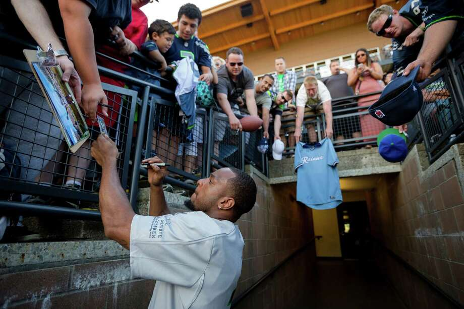 Percy Harvin signs memorabilia for fans in between innings during the Richard Sherman Celebrity Softball Game Sunday, July 7, 2013, at Cheney Stadium in Tacoma, Wash. The family-friendly event featured a home run derby with a portion of all proceeds going to Blanket Coverage, The Richard Sherman Family Foundation and Homes for Heroes. Photo: JORDAN STEAD, SEATTLEPI.COM / SEATTLEPI.COM