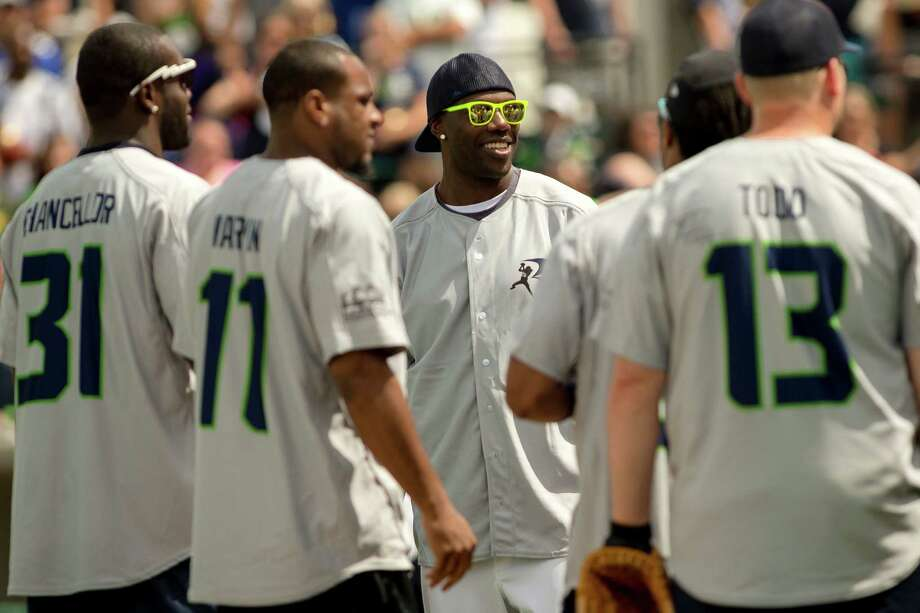 T.O. laughs with teammates between innings at the Richard Sherman Celebrity Softball Game Sunday, July 7, 2013, at Cheney Stadium in Tacoma, Wash. The family-friendly event featured a home run derby with a portion of all proceeds going to Blanket Coverage, The Richard Sherman Family Foundation and Homes for Heroes. Photo: JORDAN STEAD, SEATTLEPI.COM / SEATTLEPI.COM