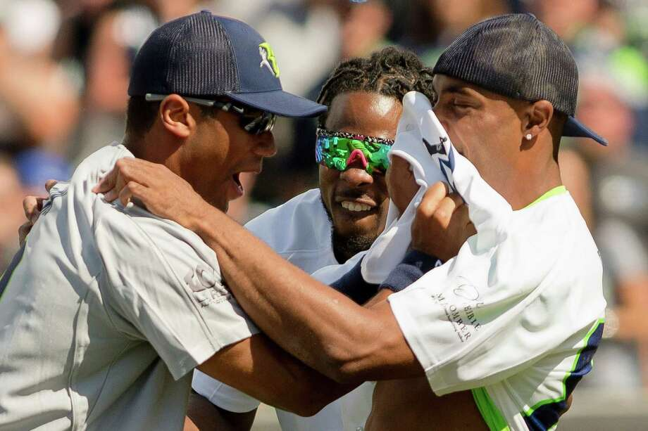 Richard Sherman, center, helps to instigate a Russell Wilson fight during the Richard Sherman Celebrity Softball Game Sunday, July 7, 2013, at Cheney Stadium in Tacoma, Wash. The family-friendly event featured a home run derby with a portion of all proceeds going to Blanket Coverage, The Richard Sherman Family Foundation and Homes for Heroes. Photo: JORDAN STEAD, SEATTLEPI.COM / SEATTLEPI.COM