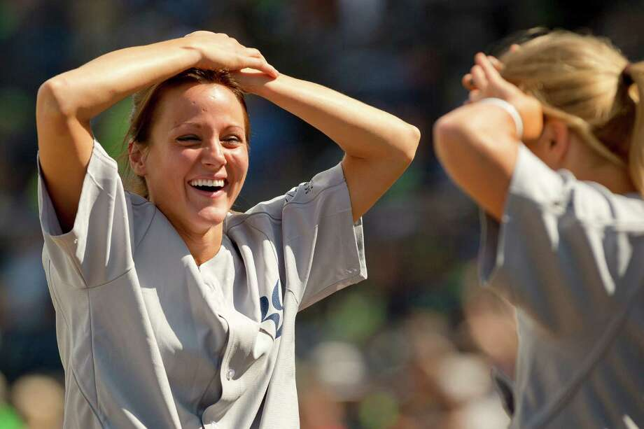 Laurel Creel, left, quarterback for the Seattle Mist, laughs with a teammate following a botched play during the Richard Sherman Celebrity Softball Game Sunday, July 7, 2013, at Cheney Stadium in Tacoma, Wash. The family-friendly event featured a home run derby with a portion of all proceeds going to Blanket Coverage, The Richard Sherman Family Foundation and Homes for Heroes. Photo: JORDAN STEAD, SEATTLEPI.COM / SEATTLEPI.COM